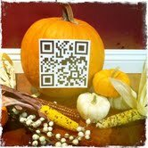 Large pumpkin with a QR code imposed on it, surrounded by smaller pumpkins, colored corn and other fall items.