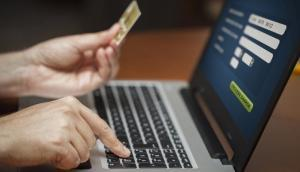 Closeup of hands holding a credit card and typing info into a laptop, representing a marketing budget