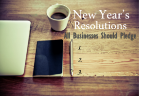 """A rustic wood table with a half-empty coffee cup, black notebook, pen and half-visible laptop with the words """"New Year's Resolutions All Businesses Should Pledge 1. 2. 3. """""""